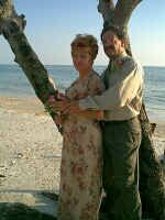 Couple hug in the shade by the ocean