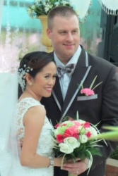 A tall man stands next to his bride who holds beautiful flowers and looks radiant in white dress