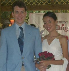 A pretty woman from the Philippines stands arm in arm with her new Hawaiian husband