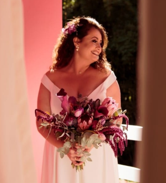 A beautiful Brazilian Christian bride poses with her wedding flowers