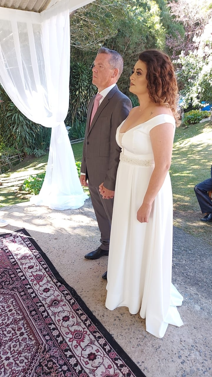 A Christian couple stand hand in hand at their wedding
