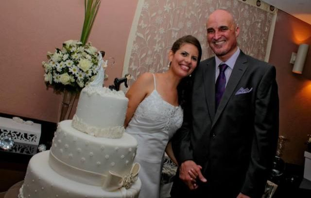 A newly wedded Christian couple laughs uncontrollably while standing behind their wedding cake