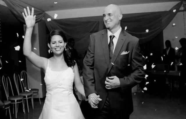 A Brazilian Christian woman holds her hand up in victory while the other holds her new husband, who laughs and walks proudly