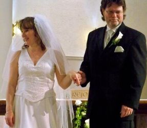 A very proud man holds his wife's hand on their wedding day