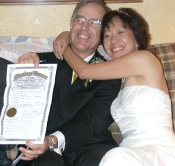 An overjoyed senior Christian woman hugs her new husband who laughs while holding up their marriage license