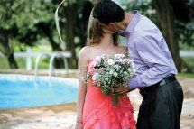 A man holds his new wife and kisses her passionately beside a pool