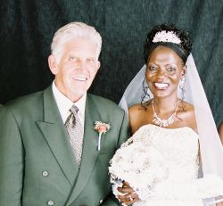A senior Christian man stands next to his beautiful new bride, who beams with joy