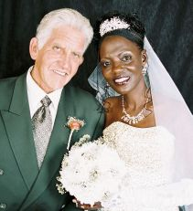 A very happy man leans next to a beautiful Christian woman in bridal dress and veil