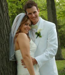 A beautiful American Christian woman hugged by her Canadian Christian husband near a tree