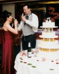 Bride and groom stand next to their wedding cake while toasting each other