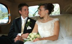 English Christian couple laugh together in their wedding car