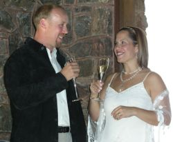 A pretty bride toasts her new husband who laughs with her