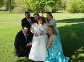 A wedding party surrounds a beautiful bride on the grass on her wedding day