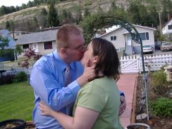 Groom can't stop himself kissing his new bride on the front lawn