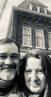 Christian couple take selfie in front of house in the city
