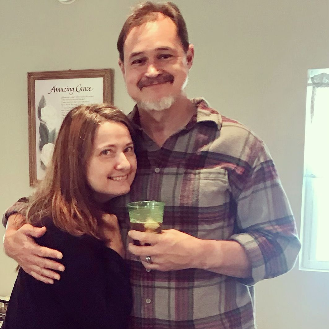 A happy Christian couple hugging while having a drink