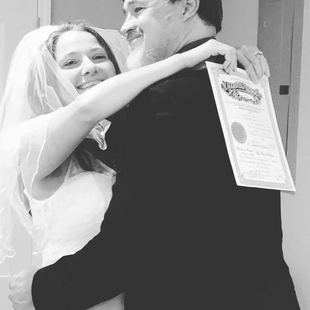 Christian bride shows proof of marriage as she hugs husband