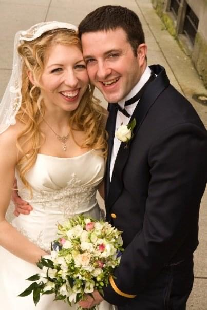 Newly married Christians laughing while looking at camera