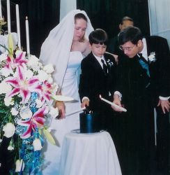 Christian singles meet at church and marry. Shown here on their wedding day behind beautiful flowers