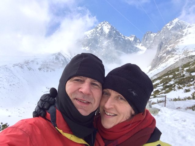 Mountain vacation for Christian couple with mountains behind them as they snuggle in winter clothes
