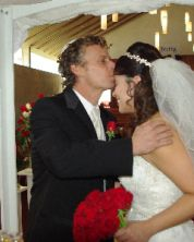 A former single Christian kisses his new wife's head as she smiles