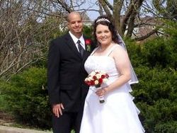 A very happy bride and groom pose outside for their April wedding