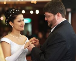 A beautiful bride looks at her new husband lovingly as he places a ring on her finger