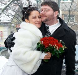 A man tenderly hugs a beautiful woman who holds flowers in a winter setting