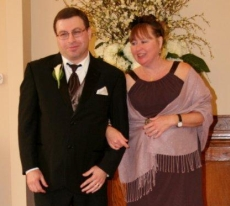 A beautiful woman stands in front of flowers with her arm linked with a handsome man in a suit