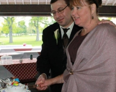 A man tenderly puts his arm around a kind looking woman as she cuts a cake