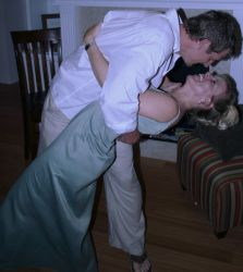 A man dips a woman for a passionate kiss as she laughs