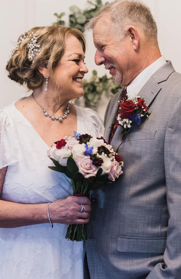 Senior Christian couple laughing while looking at each other after marrying