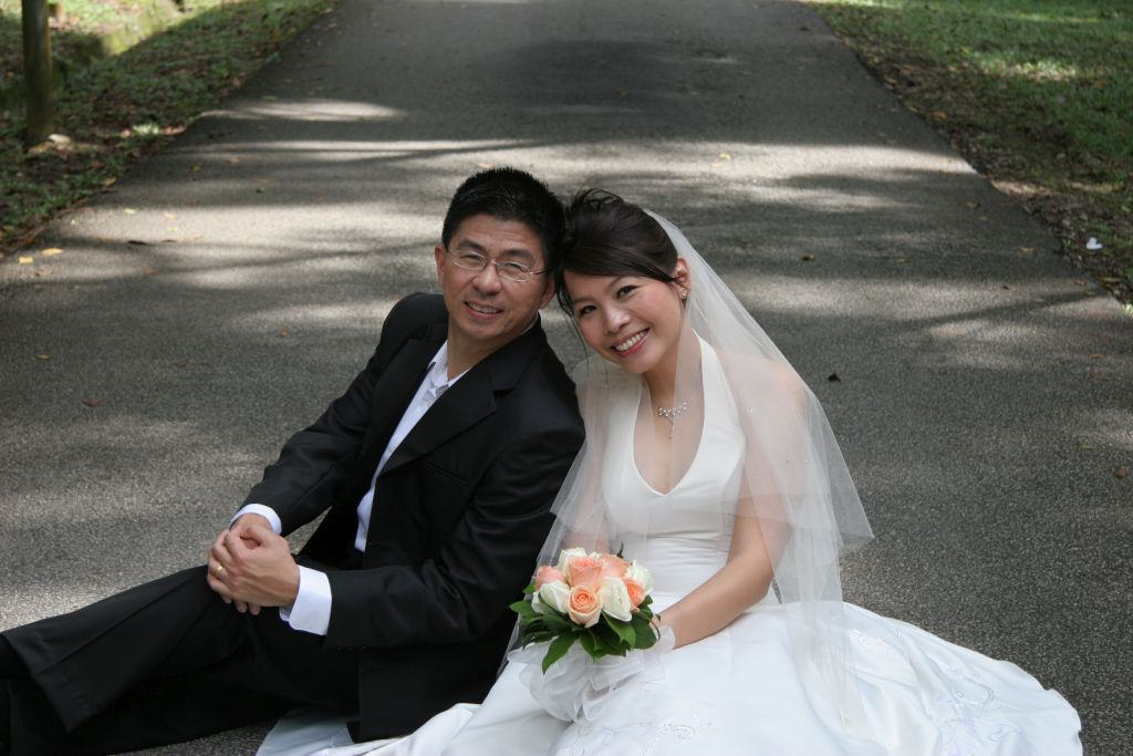 Christian newlyweds smiling and sitting on pavement just after marrying