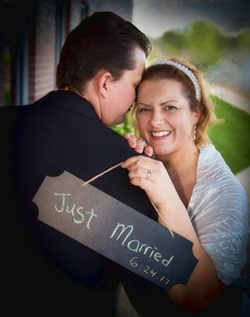 Wife smiling ear to ear while hugging new husband and holding Just Married sign