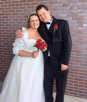 A joyful bride in beautiful white wedding dress and red bouquet is hugged by her husband in tuxedo