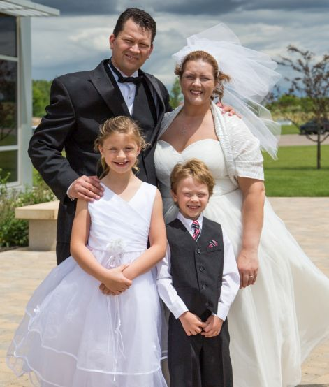 Blended Christian family standing together in heavy winds