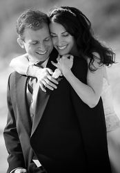 A woman laughs and is the picture of comfort as she hugs a man from behind