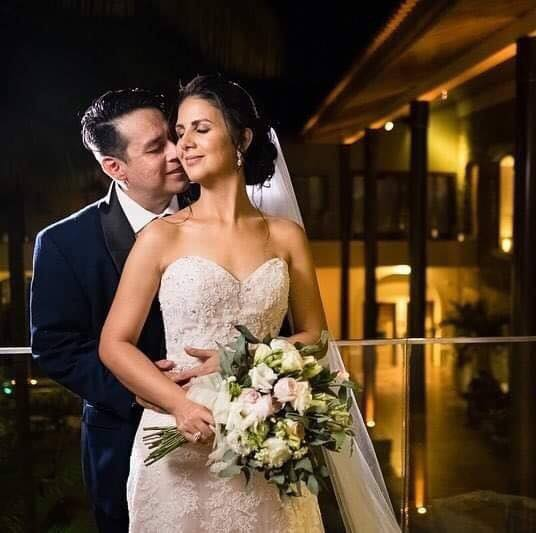 A groom lovingly kisses his bride's neck as she holds her flowers and closes her eyes