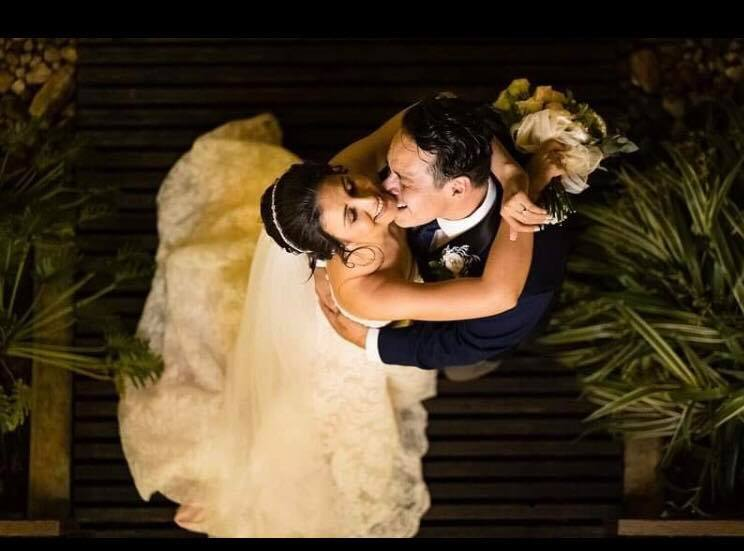 Newly married Christians are seen from above, holding each other and laughing