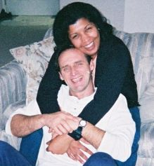 A woman laughs on the couch as she hugs a joyful man