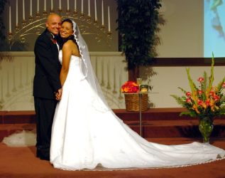 A very happy newly married Christian couple stand cheek to cheek at the altar