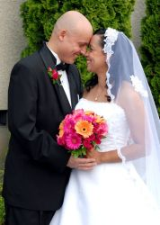 Groom leans in for a kiss from his smiling bride who holds flowers