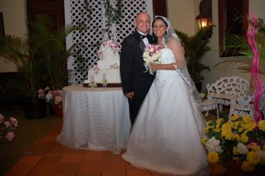 Excited Christian couple smile together next to their wedding cake