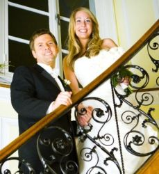 A couple stand hand in hand on a staircase and smile