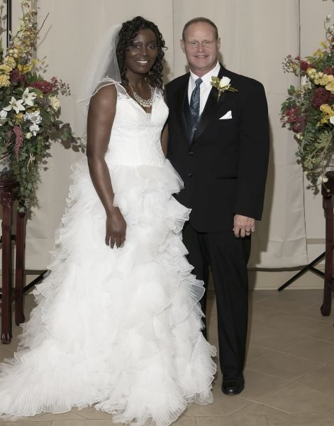 Smiling couple after marrying and flanked by beautiful arrangement of flowers