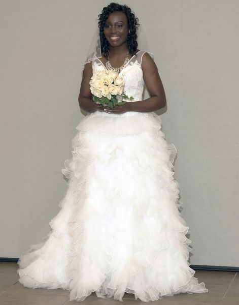Beautiful bride in white dress posing with her bouquet of flowers