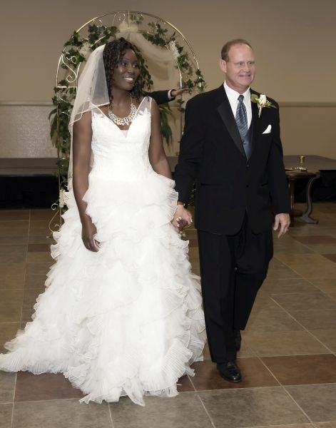 Newly married Christian couple walk into reception hall hand in hand