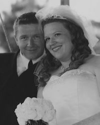 Tom and Stacy smile together on their wedding day near a pond