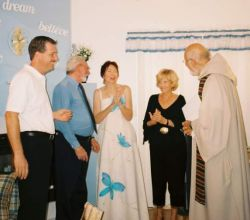 A bride claps her hands with joy as she stands next to her new Christian husband