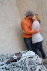 An engagement ring is shown with a newly engaged couple kissing in the background